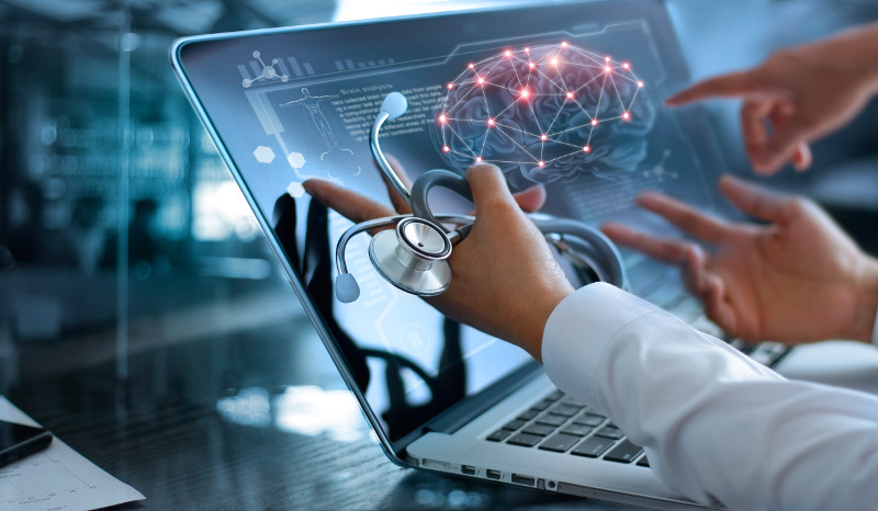 doctors pointing to a laptop screen of brain illustration